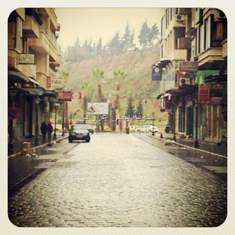 شارع ابن الرشد ويظهر بالصورة جزء من قلعة حماة