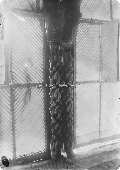 عامود رخامي مزدوج بين النافذتين الجنوبيتين تتشابك  أربع افاعيٍ تُشكل بالتفافها تضفيرة جميلة