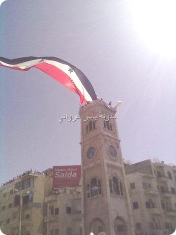 علم سوريا على ساعة حماة